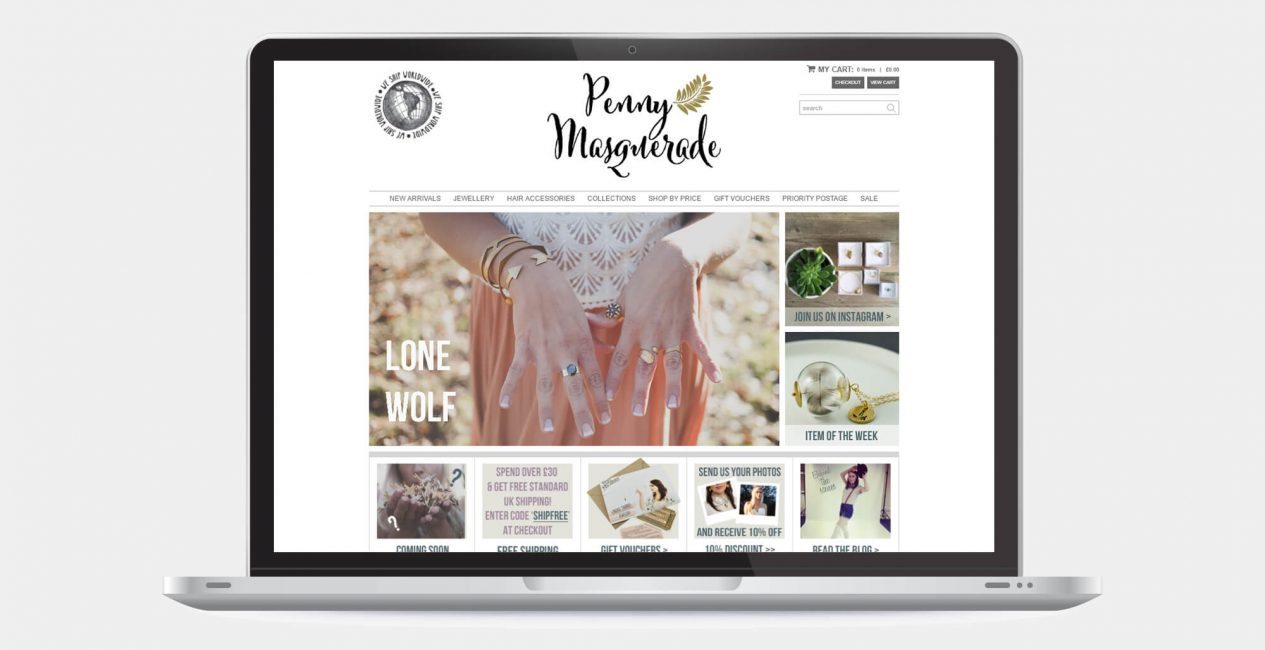 A laptop displaying the Penny Masquerade website designed by Green Route Media.